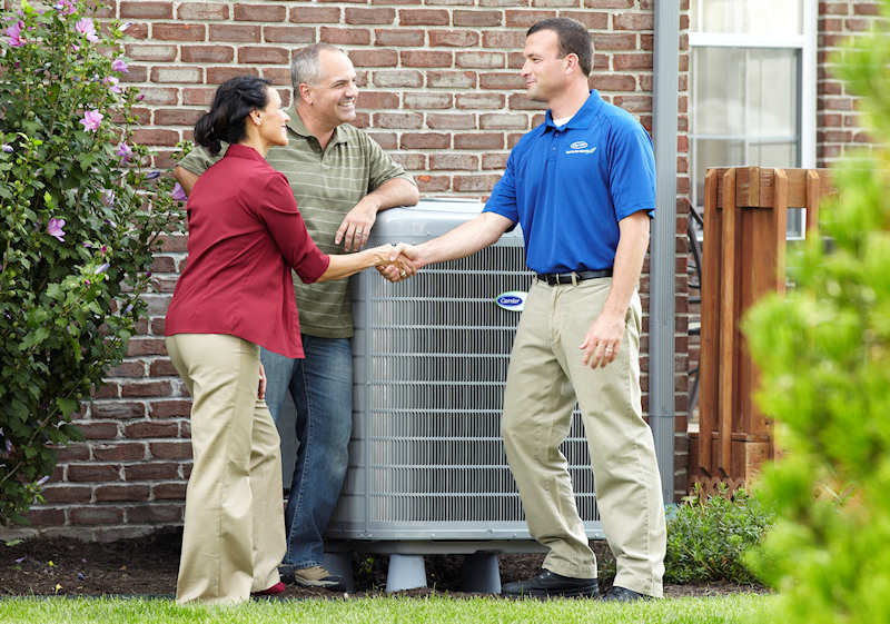 Man shaking homeowners hand near an air conditioning unit